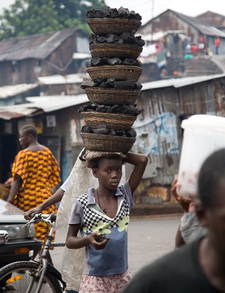 FREETOWN, SIERRA LEONE - AUGUST,2006:  Kroo Bay in the capital Freetown. Young girl carrying 6 baskets of coal on her head, which are used for cooking in the neighborhood where the running water and electricity is still remains unavailable. (Photo by: Christopher Herwig)