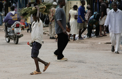ARKIV 060803 -Young boy carrying a rooster under one arm while balancing a bundle on his head crosses busy Fenton road in downtown Bo.  Bo is Sierra Leone's second largest city and is in the heart of Mende country. The area is rich in diamonds and suffered greatly during the recent civil war. Bo, Sierra Leone Foto: Christopher Herwig - Kod 9266