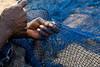 Close up of hands mending a net