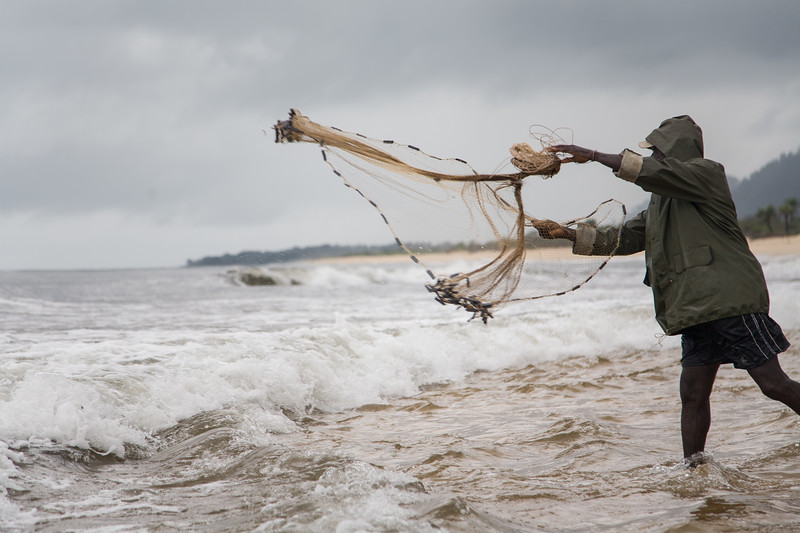 Senior man casts his nets into the sea on a stormy day