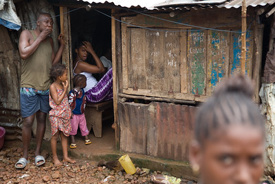 FREETOWN, SIERRA LEONE - AUGUST,2006:  Family at the entrance to their home. The underdeveloped district of Kroo Town. (Photo by: Christopher Herwig)