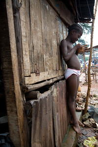 FREETOWN, SIERRA LEONE - AUGUST,2006:  Young girl leaning up against her home. The underdeveloped district of Kroo Town. (Photo by: Christopher Herwig)