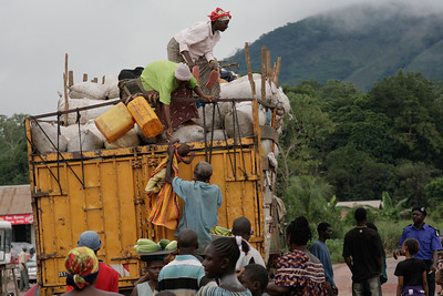 ARKIV 060803 - Baby being lowered from the top of a truck loaded with cargo and passengers ontop. Moyamba Junction. Road to Bo, Sierra Leone Foto: Christopher Herwig - Kod 9266