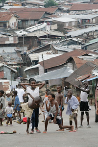 FREETOWN, SIERRA LEONE - AUGUST,2006:  Kids playing football ( soccer ) on the busystreets of Kroo town. (Photo by: Christopher Herwig)