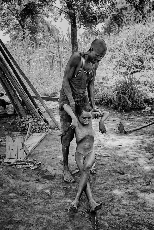 Unable to stand this particular morning, Samuel's father pulls him a short distance out of the increasingly hot sun and into the shade in preparation for a hot bath.