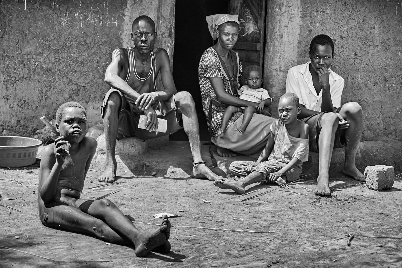 During a brief morning respite at their home, Samuel's family (father, mother, two younger sisters, and an older cousin) sit partially shaded as Samuel finishes eating a mango from a nearby tree.