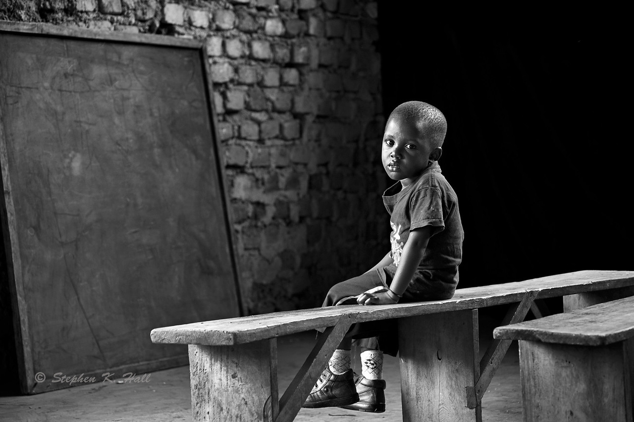 Young AIDS orphan sitting on classroom bench. Agape Children's home, Mafubira, Uganda (Summing up photo)