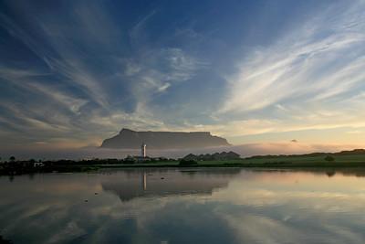 Milnerton lighthouse, Table Mountain in background, sunset