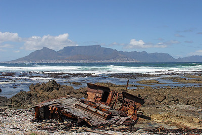 Rusted carcass of a shipwreck lies on the shores of Robben Island, Table Mountain and Cape Town in background.