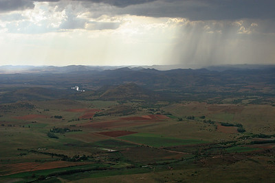 A passing summer rain shower falls across the mountainous collar of the Vredefort Dome