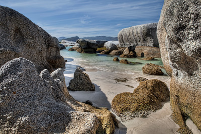 Boulders Bay, Simons Town, South Africa  After climbing over and crawling under the large boulders here I began my walk back to the entrance. On the way I made sure to get a few shots of the surreal beachfront scenery and Boulder Bay. This shot is a combination of 7 exposures, first aligned in Photoshop and then merged into one image in Photomatix before returning to Photoshop for last touches.   Click here for more on this shot at the Traverse Earth blog.   If you're interested in my HDR techniques, visit my  FREE HDR TUTORIAL.
