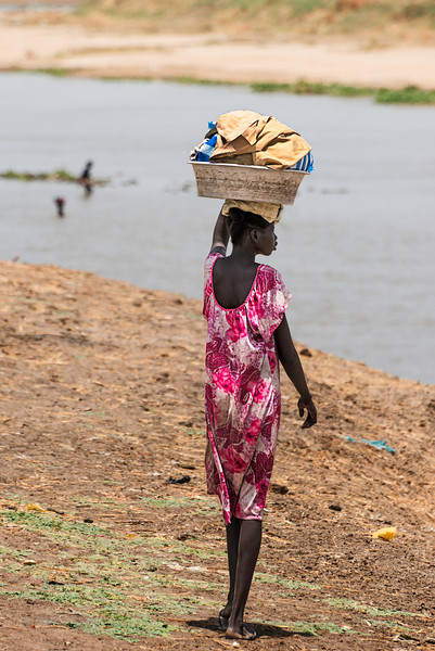 Morning wash. Young woman approaching Sobat River with basin of clothes