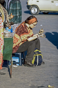 Feamle tourist enjoys hennah painting on her hands.