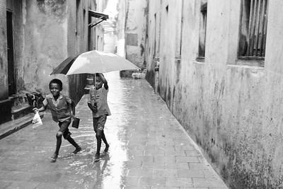 Zanzibar boys with umbrella in the rain