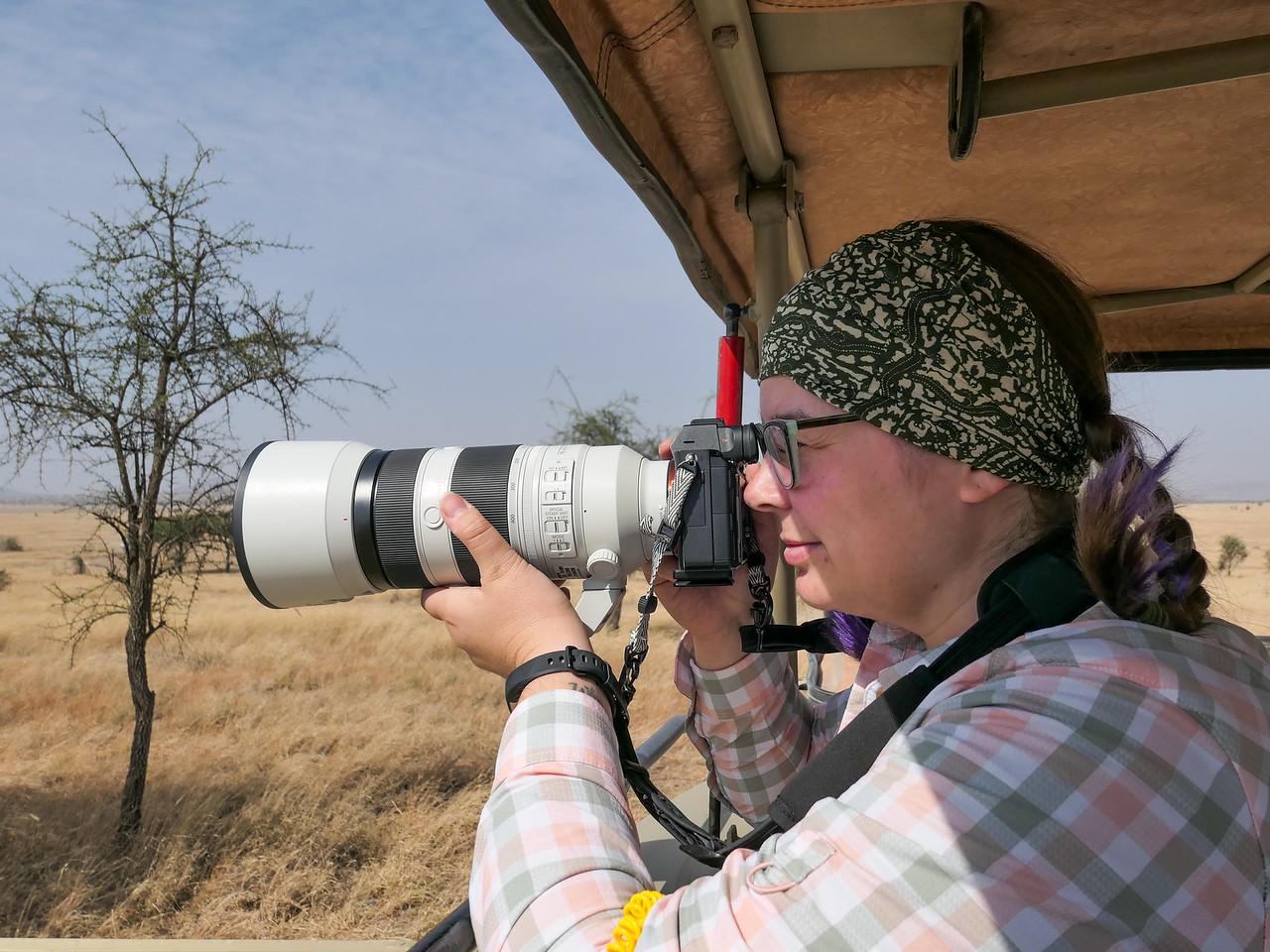 Amanda using a huge camera lens in Tanzania