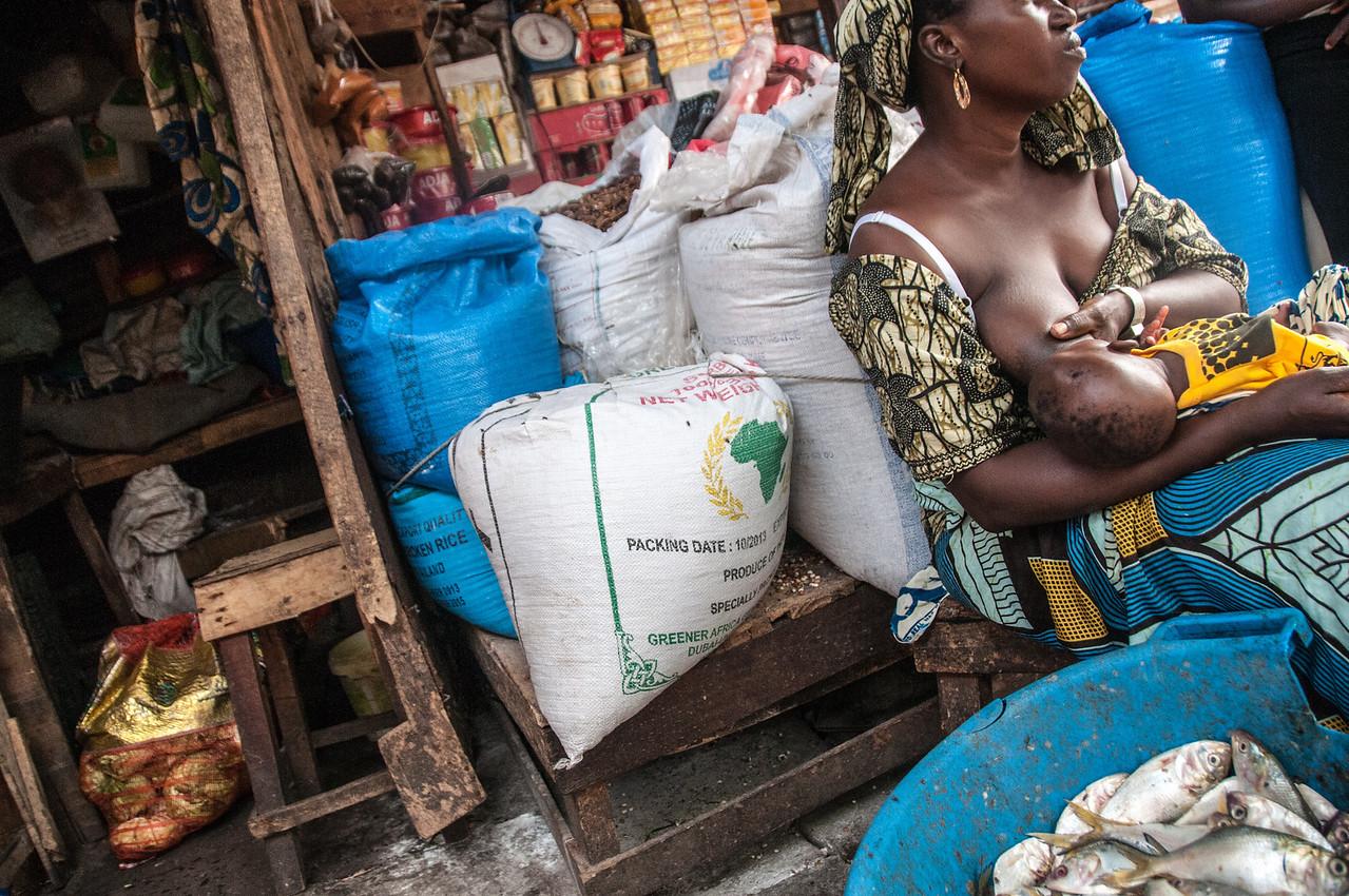 Female vendor feeding child in a market in Banjul, Gambia