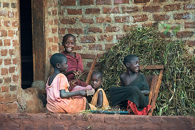 Four young girls shelling beans on doorstep, evening. Kyabirwa, Uganda.