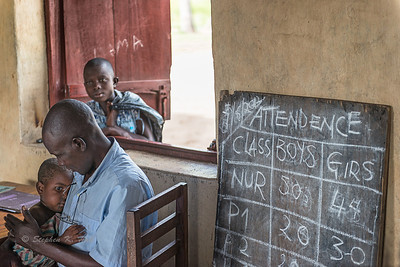 Classroom comfort. Teacher and young charge. Butiaba, Lake Albert, Masindi District, western Uganda