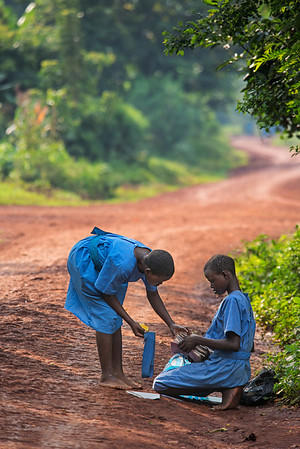 Brief stop on the way home. Two school girls sort through their books under the shade of a nearby tree. Kyabirwa, Uganda