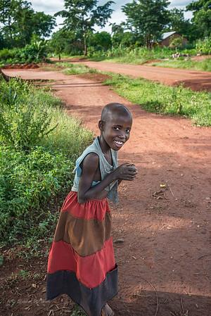 Shy young girl walking home near Lake Kyoga.  Kamuli district, Uganda