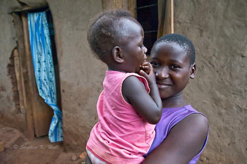Mother holding child, doorway. Jinja district, Uganda
