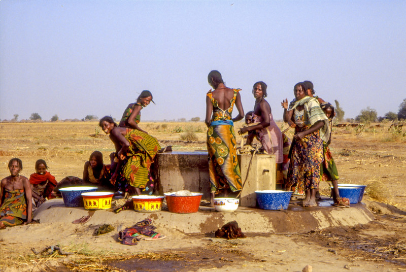 The village in the background of these vast plains we find women and children getting the eveneing water from a fountain.