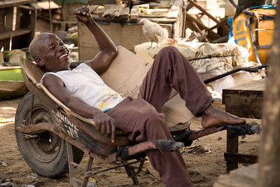 ARKIV 060908 -Vfah, the v is silent, retired government soldier waiting for his settlement from the government. Wheel barrow workers in Monrovia can be found thoughout the city in the thousands. Many belong to one of the unions, the most popular being NAWOUL -  NAtional Wheelbarrow Operators Union of Liberia. Wheelbarrow boys are divided in two main groups -  those selling products from the wheel barrow like food,  clothing, household goods, and music, while another group with those hired for transporting items.Many of the wheelbarrow boys are ex combatants from the long and brutal civil war.  For most wheelbarrow boys, the money earned is barely enough to survive on. Monrovia, Liberia Foto: Christopher Herwig - Kod 9266