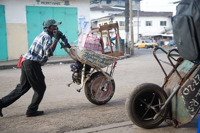 Name: Saywah Saywah - Wheelbarrow name: 747 - Slogans on the side of painted wheelbarrow: Anything can happen and No food for lazy man - 11years pushing the wheelbarrow  Randal Street,NAWOUL Zone 20 Central Monrovia. Monrovia, Liberia Foto: Christopher Herwig