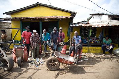 "ARKIV 060908 -Members of NAWOAL in Dwala market.  ""You know, we are wheelbarrow people, and we can be hard to find,"" says T.R. Sieh, whose laminated ID card shows that he's the [title] ""We're always out in the market carrying a load.""  Started in 1991 national wheelbarrow operators association of Liberia, or NAWAOL If you are doing wheelbarrow deliveries in this market and you're not registered, we arrest you. Joseph Cooper, Chief of Security for NAWOAL, Douala Market branch. George Wilson, Financial Secretary, NAWOAL 05637882 yellow boots 394 members Wheel barrow workers in Monrovia can be found thoughout the city in the thousands. Many belong to one of the unions, the most popular being NAWOUL -  NAtional Wheelbarrow Operators Union of Liberia. Wheelbarrow boys are divided in two main groups -  those selling products from the wheel barrow like food,  clothing, household goods, and music, while another group with those hired for transporting items.Many of the wheelbarrow boys are ex combatants from the long and brutal civil war.  For most wheelbarrow boys, the money earned is barely enough to survive on. Monrovia, Liberia Foto: Christopher Herwig - Kod 9266"
