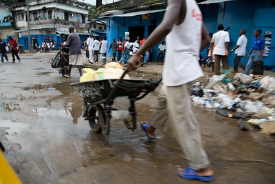 ARKIV 060908 - Wheel barrow workers in Monrovia can be found thoughout the city in the thousands. Many belong to one of the unions, the most popular being NAWOUL -  NAtional Wheelbarrow Operators Union of Liberia. Wheelbarrow boys are divided in two main groups -  those selling products from the wheel barrow like food,  clothing, household goods, and music, while another group with those hired for transporting items.Many of the wheelbarrow boys are ex combatants from the long and brutal civil war.  For most wheelbarrow boys, the money earned is barely enough to survive on. Monrovia, Liberia Foto: Christopher Herwig - Kod 9266