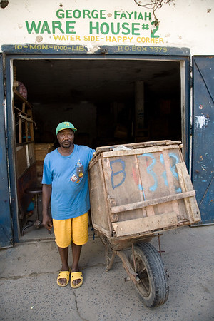 ARKIV 060908 - Joseph, Wheel barrow workers in Monrovia can be found thoughout the city in the thousands. Many belong to one of the unions, the most popular being NAWOUL -  NAtional Wheelbarrow Operators Union of Liberia. Wheelbarrow boys are divided in two main groups -  those selling products from the wheel barrow like food,  clothing, household goods, and music, while another group with those hired for transporting items.Many of the wheelbarrow boys are ex combatants from the long and brutal civil war.  For most wheelbarrow boys, the money earned is barely enough to survive on. Monrovia, Liberia Foto: Christopher Herwig - Kod 9266