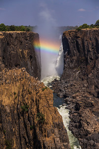 Victoria Falls, Zambia A rainbow over Victoria Falls shot from the Zambia side. As the sun rises higher in the sky, the rainbow moves further down on the waterfall.