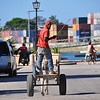 A man with his donkey drawn chariot cruises down the main seafront road in Stone Town, Zanzibar