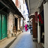 On one of the many narrow inner streets in the older part of Stone Town. Many women wear the burka, often in very bright colors. Stone Town, Zanzibar