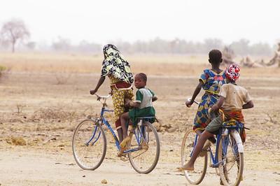 Jeunes filles à bicyclette sur la route du village