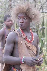 Hadzabe with handmade knife and baboon hat.