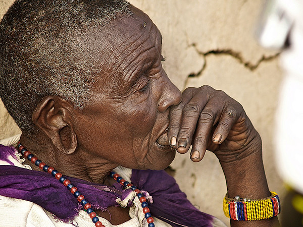 Vis gammel kone. Den eldste kvinnen i bomaen, ser tankefullt på de lettkledde og keitete hvithudene som er innom på besøk en drøy time. Masai Mara, oktober 2006. *** Wise old lady. The oldest woman in the boma, watching thoughtfully at the lightly dressed and clumsy whiteskins visiting the boma for a short hour. Masai Mara, October 2006. (Foto: Geir)