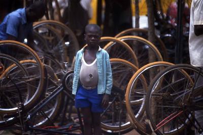 Curious boy by the bycicle mending shops at Abakaliki market, Enugu state. --- Nysgjerrig gutt ved sykkelreparatørenes skur på Abakaliki-markedet, Enugu state. (Foto: Geir)