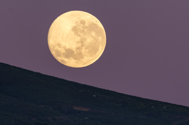 Setting of July's Blue Moon 1August 2015 against a gentle landscape slope of Table Mountian base