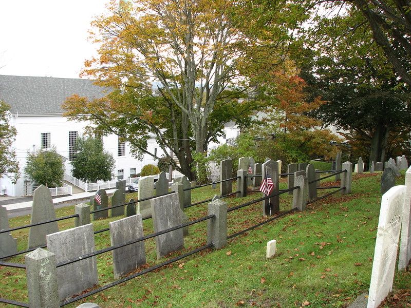 The Thacher family plot can be easily found. Enter the cemetery via the main entrance (School Street at Town Square.) Climb the stairs and continue up the brick path to the top of the hill. Turn sharp right here and walk between graves going a little downhill. The Thacher plot is the only one with an iron railing enclosure. Dr. Thacher's gave is the one with the flag.