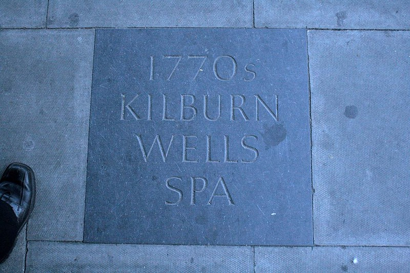 At the time of the duel, Kilburn Wells was a place with iron-rich water and gardens in a rural area north of London. Today all has been built over, but there are markers to commemorate the place. This one is set into the sidewalk at the intersection of Belsize Road and Kilburn High Road, near the Kilburn High Road London Overground Station.