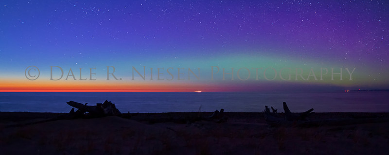 The blues, magentas and greens of the Aurora Borealis (Northern Lights) do battle with the setting sun at twilight over Lake Superior along the sand dunes of Whitefish Point.  Captured as the after glow of the setting sun gave way to the stars and aurora.  Taken on 5/6/2013 north of Paradise, Michigan.  Note: Special steps may need to be taken when ordering a panoramic image please review the panoramic print sizes for cropping. However there are a number of sizes that appear to be perfect fits without cropping for this photo from an 8 x 20 to a 20 x 50 panoramic size print .