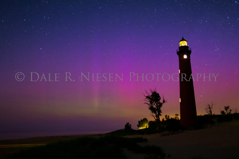 The northern lights and Little Sable Lighthouse at Silver Lake State Park and sand dunes near the town of Silver Lake, Michigan taken Sunday July 14, 2013. Note the meteor in the center of the photo.