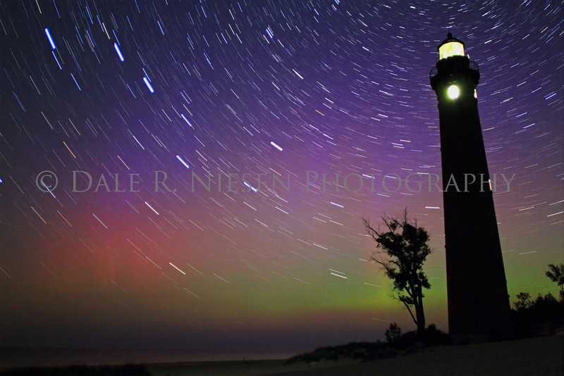 The northern lights and star trails over Little Sable Lighthouse in Silver Lake State Park and sand dunes near the town of Silver Lake, Michigan taken on the night of July 14-15, 2013.