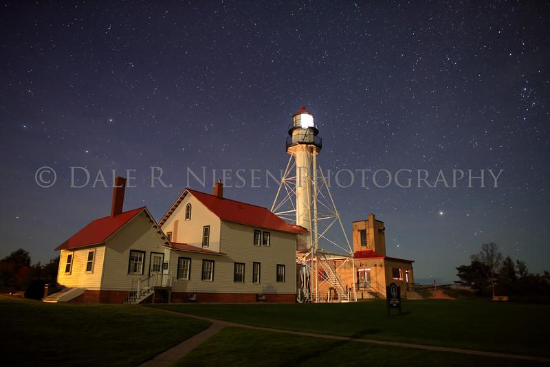 The night sky above the historic Whitefish Point Lighthouse on Whitefish Bay, Lake Superior near Paradise, Michigan.