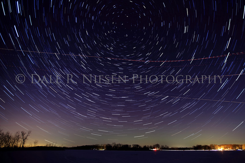 Star Trails, airplanes, a metoer and a faint purple and bluish green Aurora over Portage Lake, Jackson County, Michigan taken on the night of February 27, 2014.
