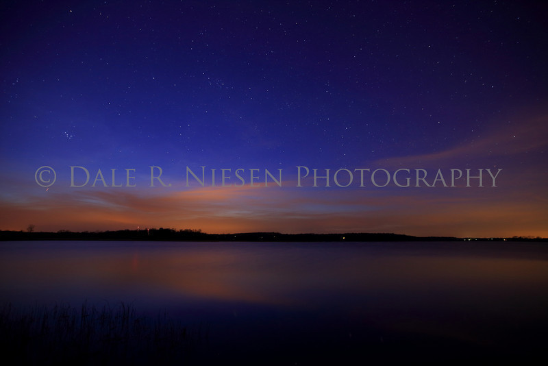 The aurora borealis, clouds and light from nearby towns reflecting off of Fourmile Lake April 19, 2014 in the Chelsea State Game Area, Washtenaw County, Michigan.