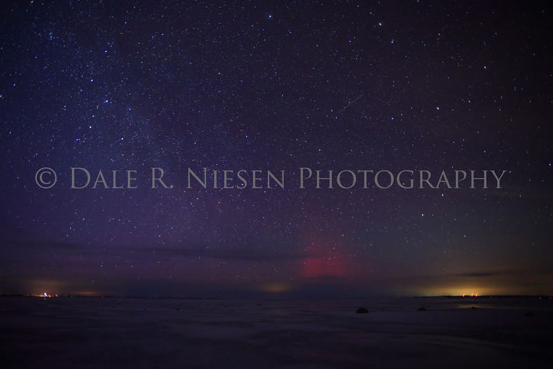 Old Mission Peninsula Aurora a faint purple and red aurora captured along with the milky way and a meteor over Grand Traverse Bay near Mission Point Lighthouse.