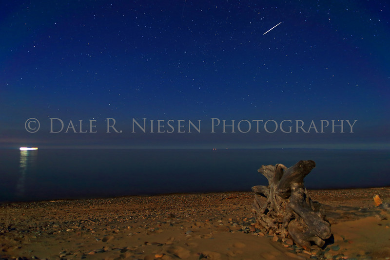 Whitefish Point June 6, 2014.  Faint aurora low at the horizon with air glow above and moon light on the beach make for soft pastel like colors in this capture over Lake Superior at Whitefish Point.   To add to the photo a satellite was captured as it made a pass overhead.