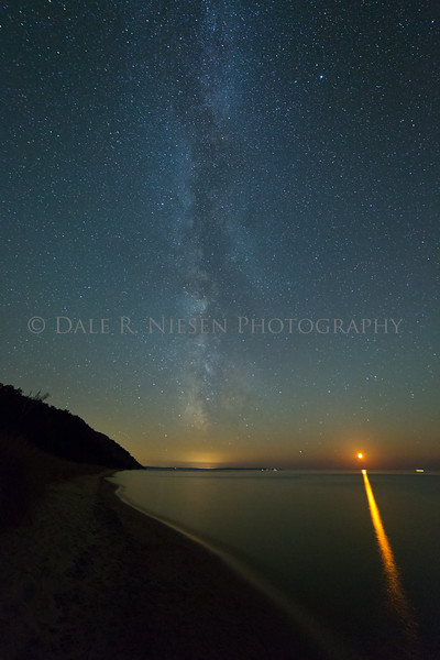 The milky way from Empire, Michigan at the Sleeping Bear Dunes National Lakeshore.  Looking south from the Empire public beach toward Frankfort, Michigan (light pollution below the milky way) as the moon sets on Lake Michigan.